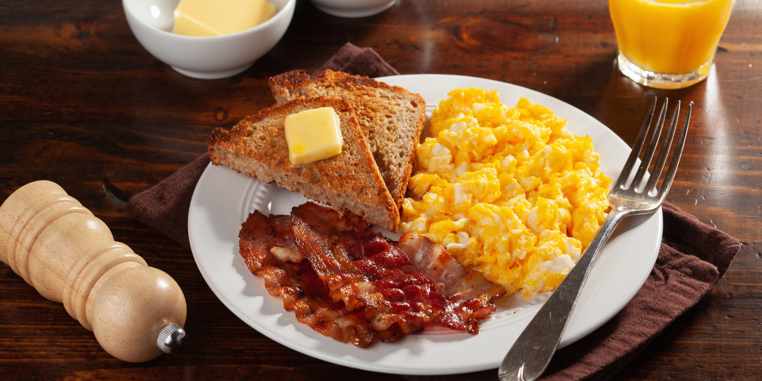traditional scrambled egg breakfast with bacon and toast